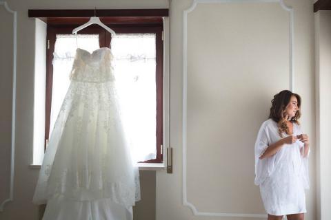 sposa pensierosa prima di indossare l'abito da sposa foto reportage