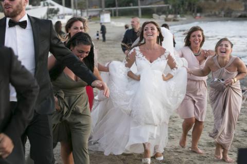 la sposa corre sulla spiaggia con i suoi amici dopo il matrimonio foto senza posa