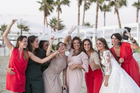 sposa e amiche sotto al velo sulla spiaggia di punta romana